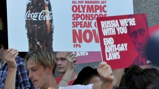 Pro-gay activists hold placards calling for Sochi Winter Olympic sponsors to speak out against Russia's anti-gay laws during a protest in Melbourne on Wednesday