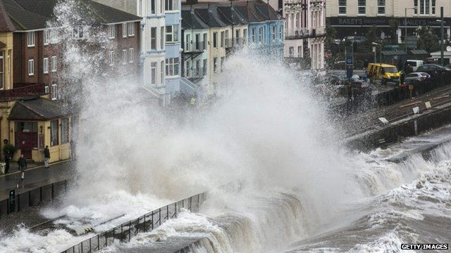 Waves crash against the seafront and railway in Dawlish on February 5