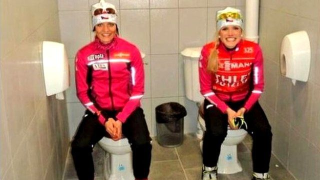 Athletes sitting on toilets side by side