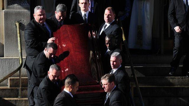 Pallbearers carry his coffin