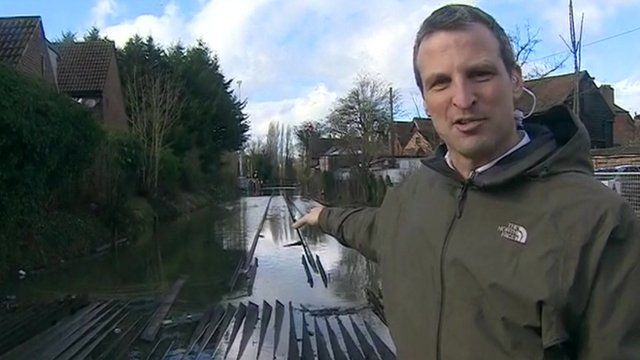 Richard Westcott pointing out submerged electric rails outside Datchet station
