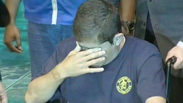 Mr Alvarenga covers his eyes as he arrives in El Salvador