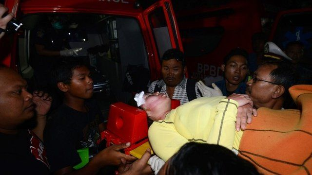 A Japanese scuba diver is carried to an ambulance