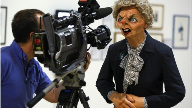 "A camera man films the Spitting Image puppet of Margaret Thatcher on display in an exhibition ""Rude Britannia : British Comic Art"" at Tate Britain"