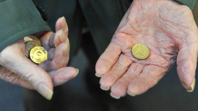 Elderly woman holding pound coins