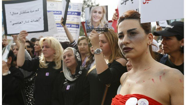 A woman with make-up made to look like a bruise walks with families of victims of domestic violence during a march against domestic violence, marking International Women's Day in Beirut