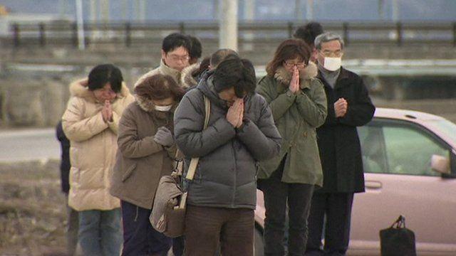 Mourners praying in Minamisanriku