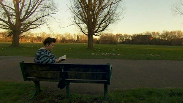 Woman sat reading on park bench