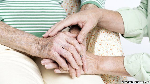 Elderly woman being comforted by a carer.