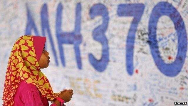 A girl looks at a board with messages of support and hope for passengers of the missing Malaysia Airlines MH370 at the Kuala Lumpur International Airport
