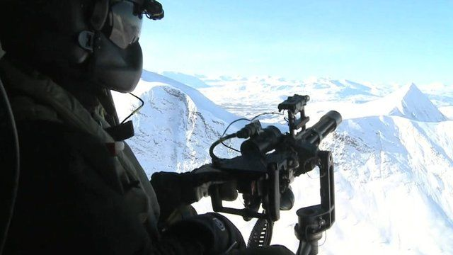 Soldier aiming gun out of helicopter in arctic