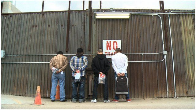 Immigrants about to be deported from US to Mexico line up against the border fence
