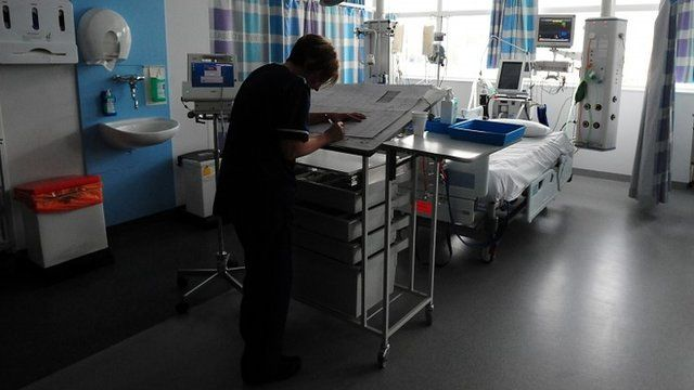 Nurse writes up notes in hospital ward
