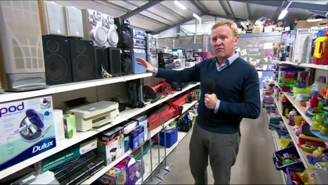John Maguire in recycle shop next to shelves of electrical goods and toys
