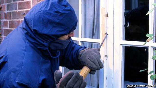 A burglar breaking into a house