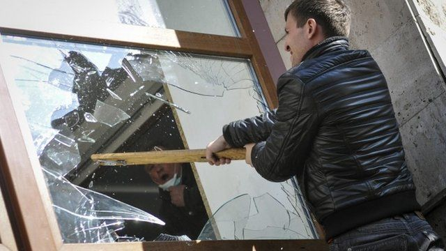 A pro-Russian protester breaks a window as they storm the regional government building in Donetsk April 6, 2014