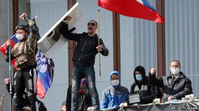 """Pro-Russian activists who seized the main administration building in the eastern Ukrainian city of Donetsk hold Russian flag and flag of so-called """"Donetsk Republic"""""""