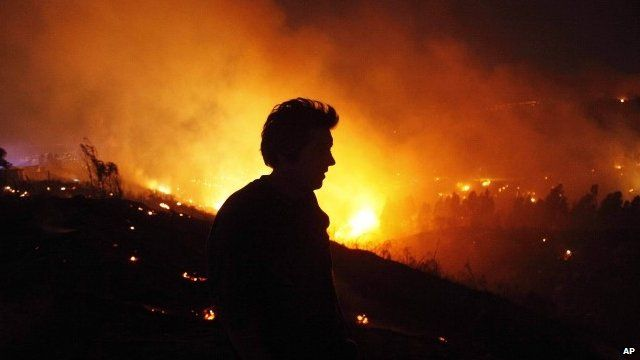 A person tries to extinguish flames during a forest fire in Valparaiso, Chile