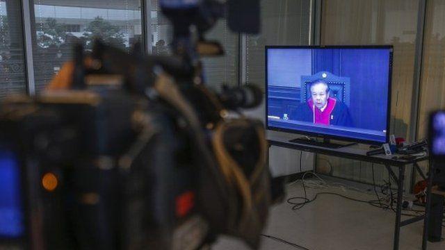 Big screen showing judge giving verdict
