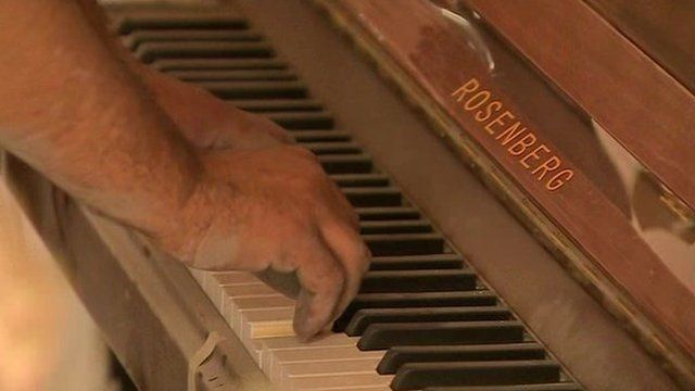 Man plays dusty piano inside Homs