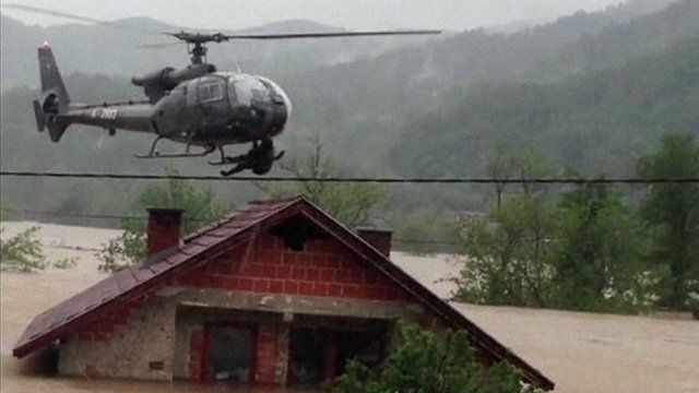 man hangs from underside of helicopter