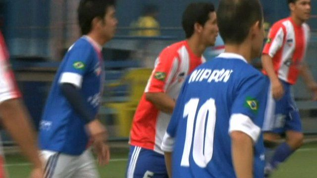 Football players from Paraguay and Japan on a pitch