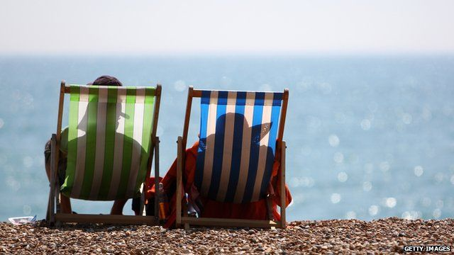 Two people sit on deckchairs on the beach
