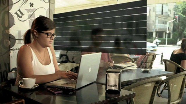 A woman in a coffee shop using a smart glass privacy screen