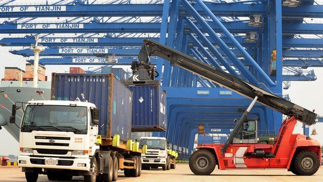 Shipping containers being loaded onto trucks from a cargo ship at Tianjin port, China