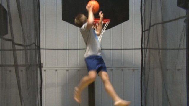 A boy playing basket ball on a trampoline at the Camberley park