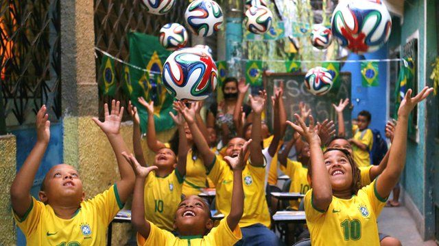 Children throwing footballs in the air