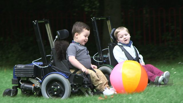 Two boys playing with an inflatable football in their chairs, which are low to the ground so they can kick it