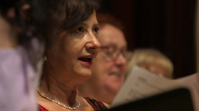 Woman singing in a choir with sheet music