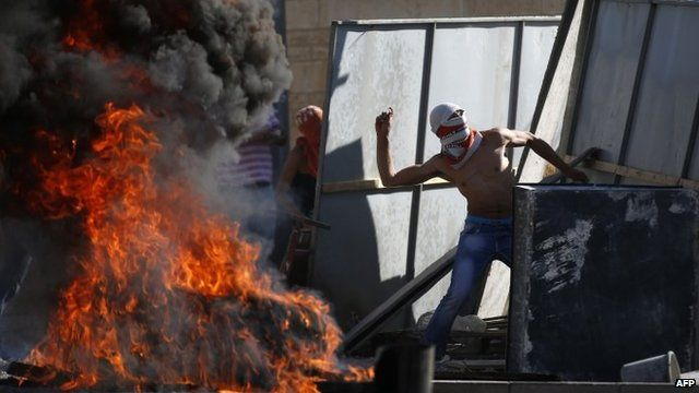 Masked Palestinian protesters throw stones towards Israeli police in East Jerusalem on 2 July 2014