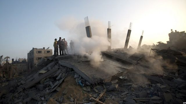 Palestinian inspect a house destroyed by an Israeli strike, 8 July 2014
