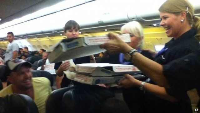 A Frontier Airlines flight attendant passes out pizza to passengers