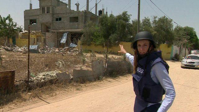 Yolande Knell pointing at damaged building