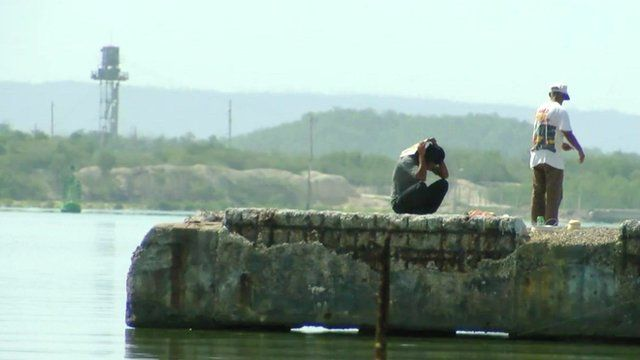 Two men on pier with Guantanamo Bay watch tower in background