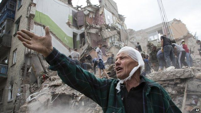 Man in front of badly damaged building
