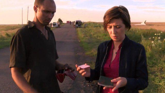 Man hands passenger belongings to Natalia Antelava