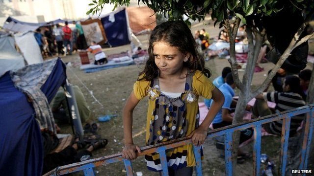 A Palestinian girl stands near makeshift tents in the garden of the Shifa hospital in Gaza City - 31 July 2014