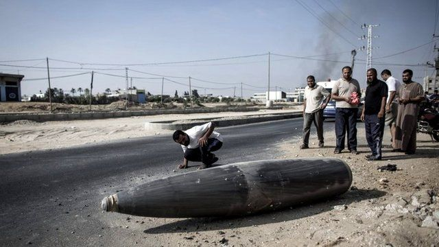 A Palestinian man inspects an Israeli warhead that failed to explode on the side of a road, during a ceasefire in Deir al-Balah, central Gaza Strip