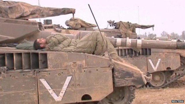 Israeli soldier sleeping on top of his tank
