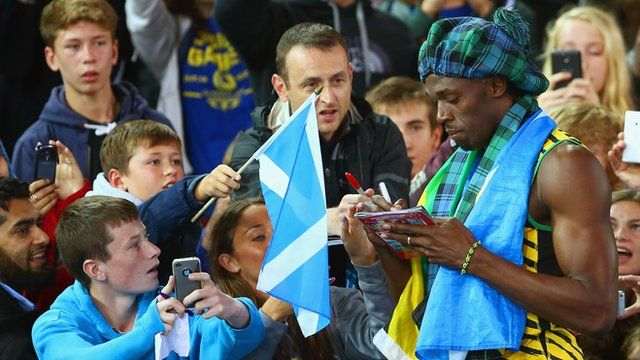 Usain Bolt signs autographs after winning the 4x100m with Jamaica