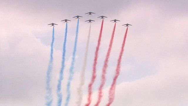 Planes trailing blue, white and red smoke