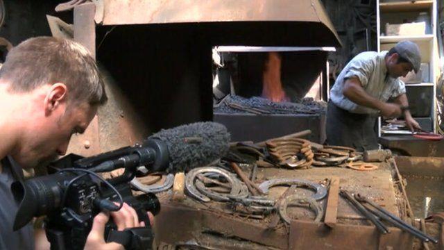 Filming a man making horseshoes