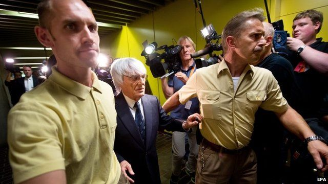 Bernie Ecclestone (C) leaves a Munich court after the end of his trial