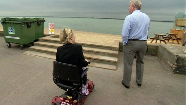 reporter in wheelchair looks at steps to beach