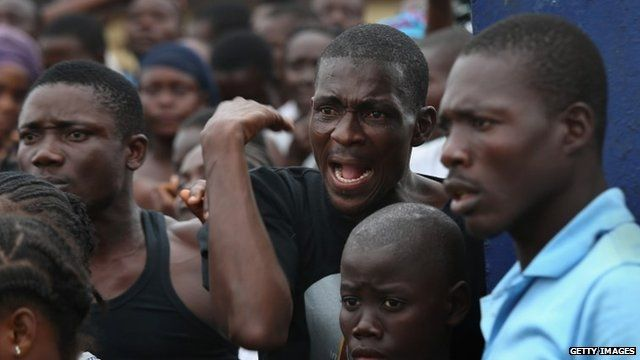 A crowd urges people in an Ebola isolation centre to come out after a mob opened the gates the facility