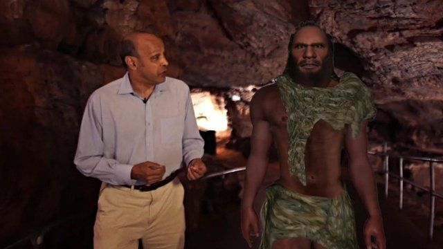 Pallab Ghosh walking next to simulation of a Neanderthal man